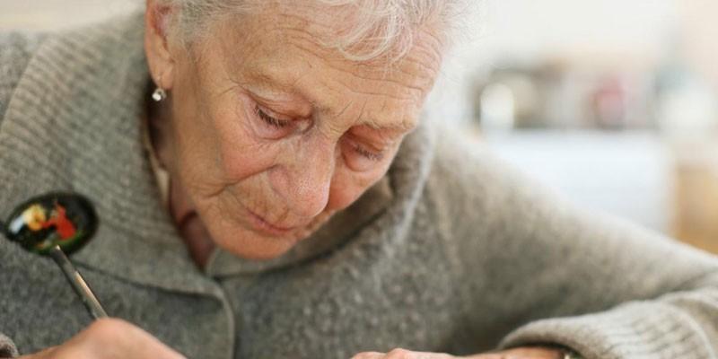 Пожилая женщина пишет