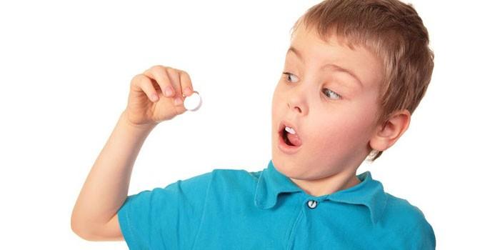Мальчик с таблеткой в руке