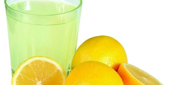 Лимонный сок в стакане и лимоны