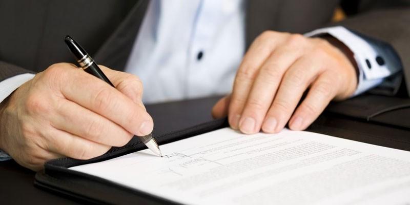 Человек подписывает договор