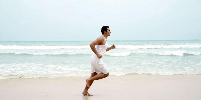 Мужчина бежит по побережью