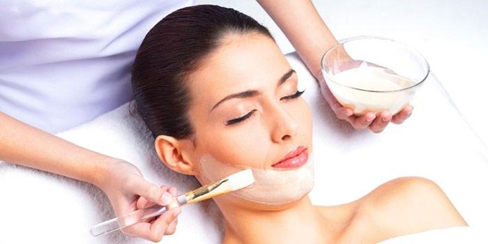 Девушке делают процедуру пилинга кожи лица