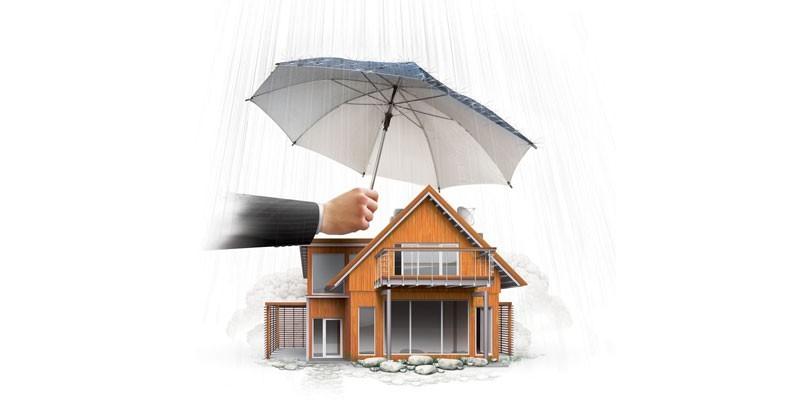 Человек держит зонтик над коттеджем