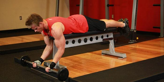 Мужчина делает упражнения со штангой