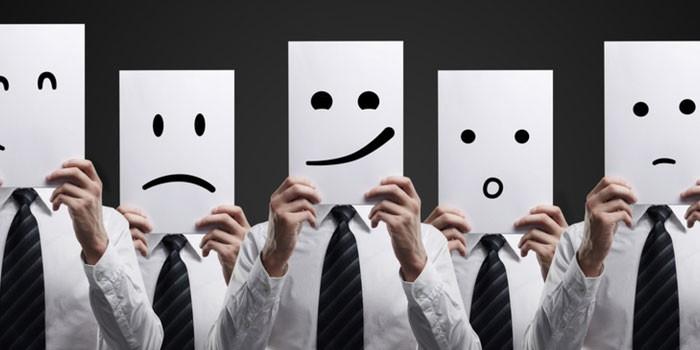 Люди закрывают лица изображениями эмоций