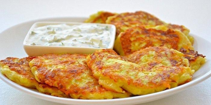 Готовые кабачковые оладьи с сыром на тарелке