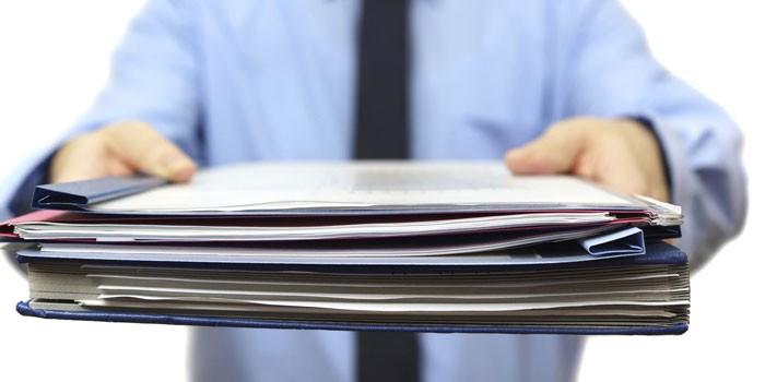 Папки с документами в руках у мужчины
