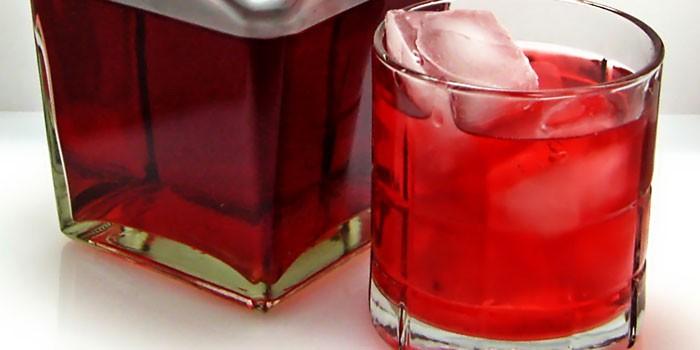 Бутылка и стакан с черносмородиновой наливкой на коньяке