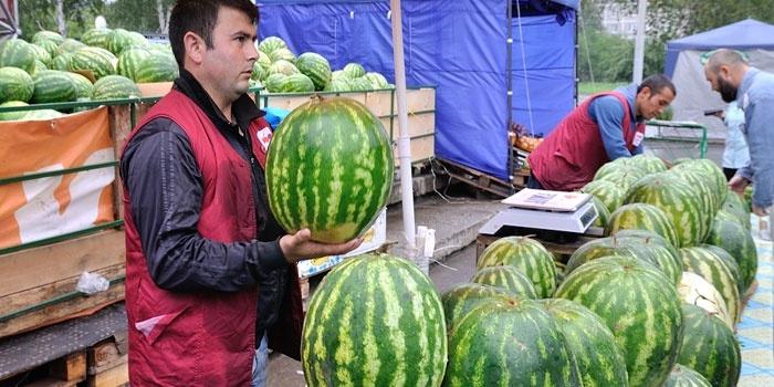 Мужчина продает арбузы