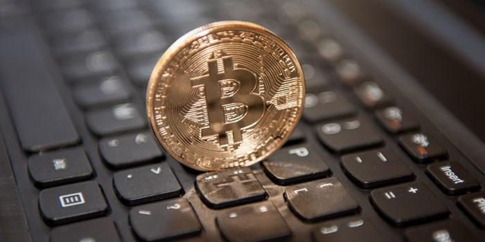 Монетка со значком биткоина на компьютерной клавиатуре