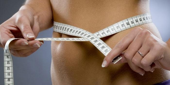 Девушка измеряет объем талию сантиметром