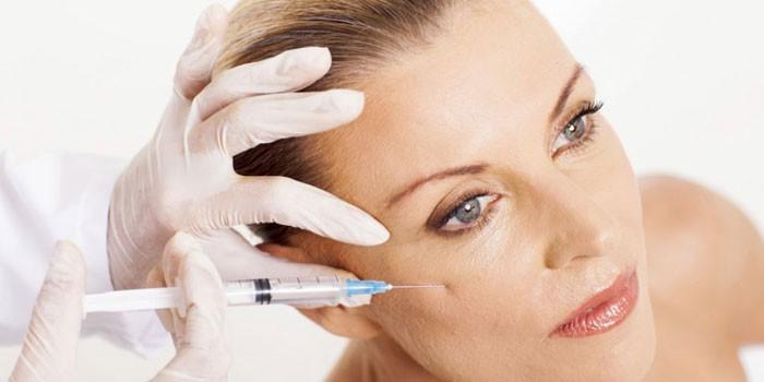 Женщине делают инъекцию в кожу лица