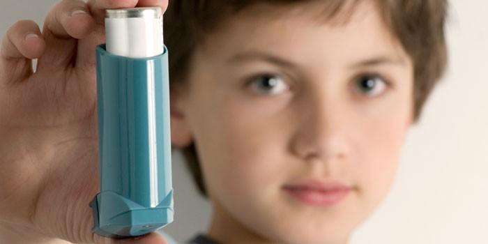 Мальчик держит в руках ингалятор