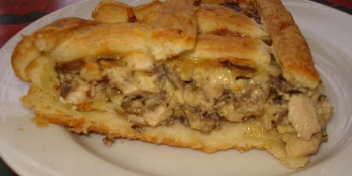 Кусочек пирога из слоеного теста с начинкой из курицы и шампиньонов