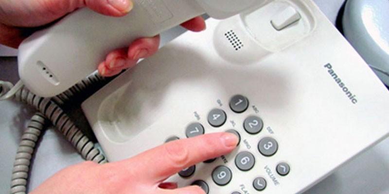 Женщина набирает номер телефона