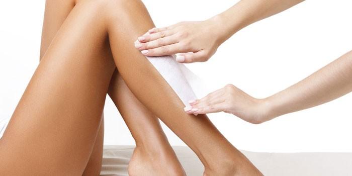 Девушке делают восковую эпиляцию на голени