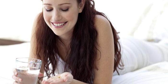 Девушка держит на ладони таблетку и стакан воды в руке