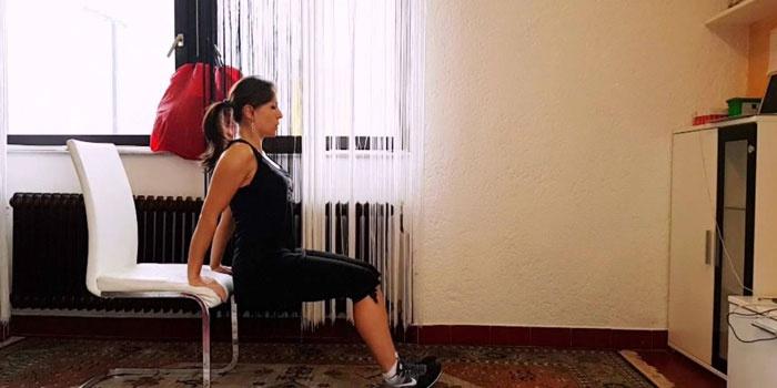 Девушка делает обратные отжимания от стула
