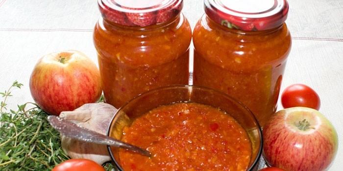 Аджика из томатов, яблок в банках и тарелке