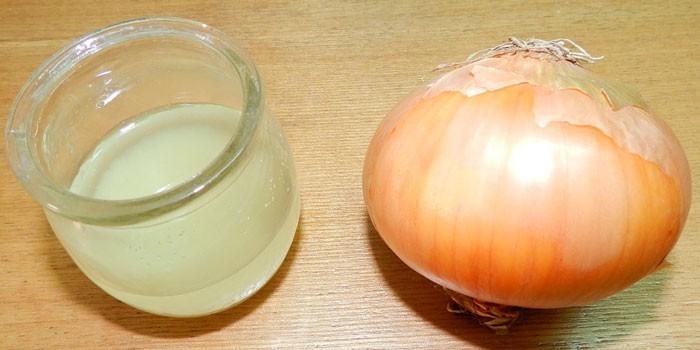 Луковый сок в стеклянном сосуде и репчатый лук