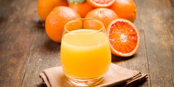 Апельсиновый сок в стакане и апельсины