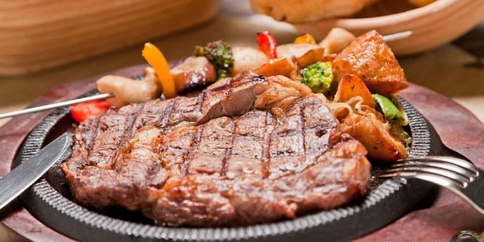 Говяжий стейк с овощами гриль на тарелке