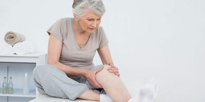Пожилая женщина в кабинете врача держится за колено