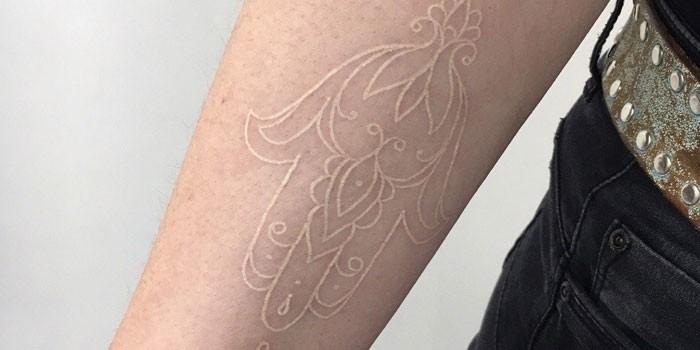 Контурная белая татуировка на руке