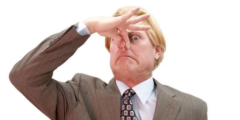 Мужчина закрывает нос пальцами руки