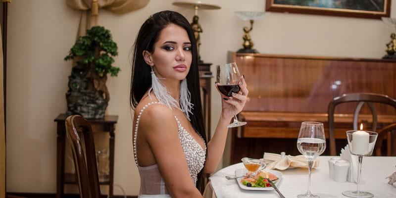 Девушка пьет вино в ресторане