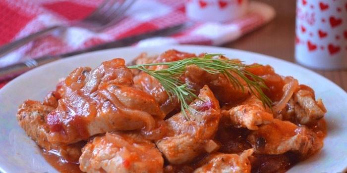 Тушеная куриная грудка в томатном соусе на тарелке