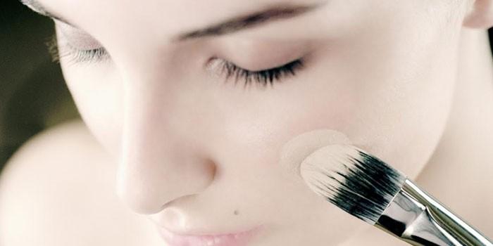Девушка наносит на лицо базу под макияж