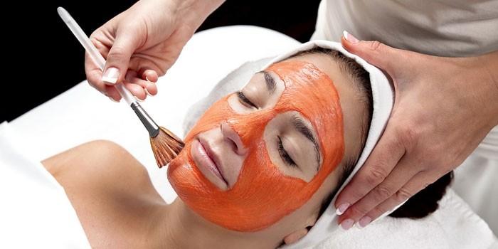 Косметолог наносит маску кистью
