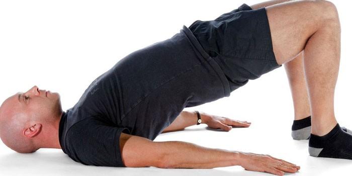 Мужчина делает упражнение Ягодичный мост