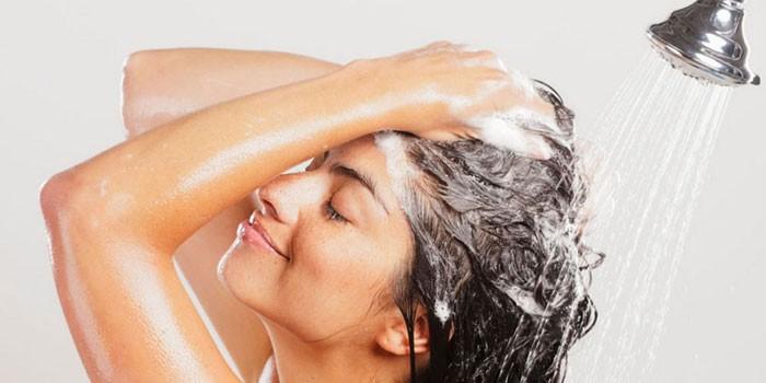 Женщина моет голову под душем