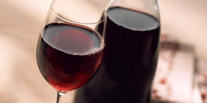 Вино из черносмородинового варенья в бокале и бутылке