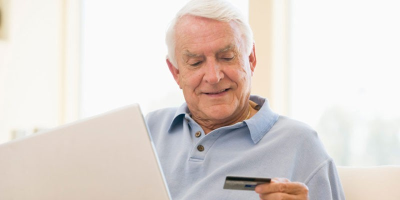 Пожилой мужчина с ноутбуком и пластиковой картой