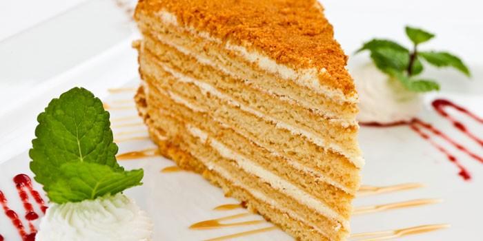 Кусочек медового торта на тарелке