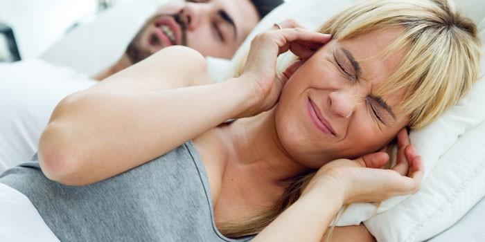 Девушка лежит с парнем в постели и закрывает уши