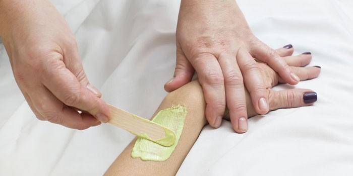 Женщине наносят воск на кожу рук