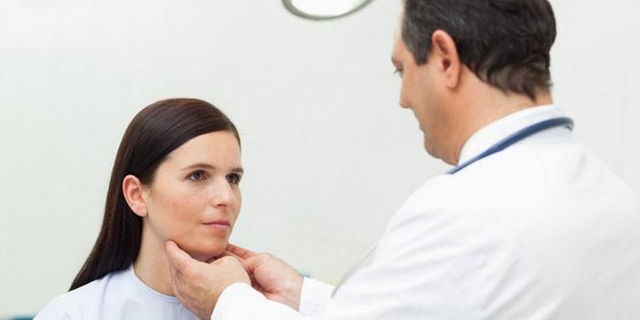 Врач осматривает горло женщины