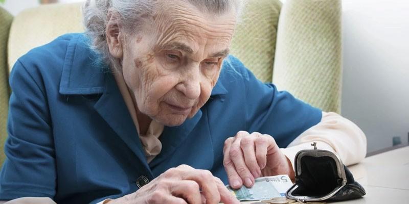 Пожилая женщина считает деньги
