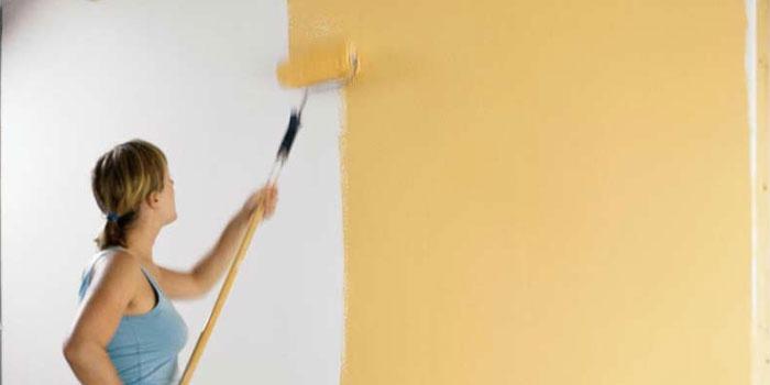Женщина красит стену валиком