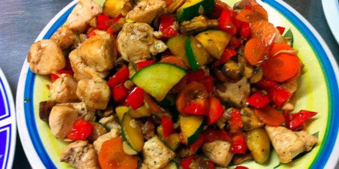 Тушеная куриная грудка с овощами на тарелке