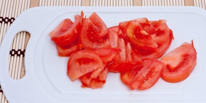 Нарезанные дольками помидоры на досочке