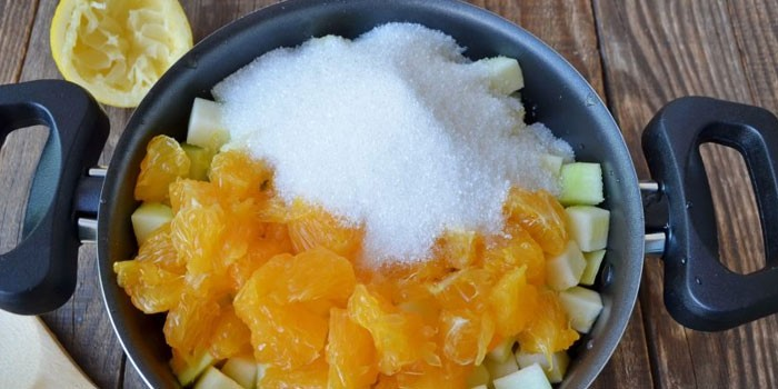 Нарезанные кабачки и апельсины с сахаром в кастрюле