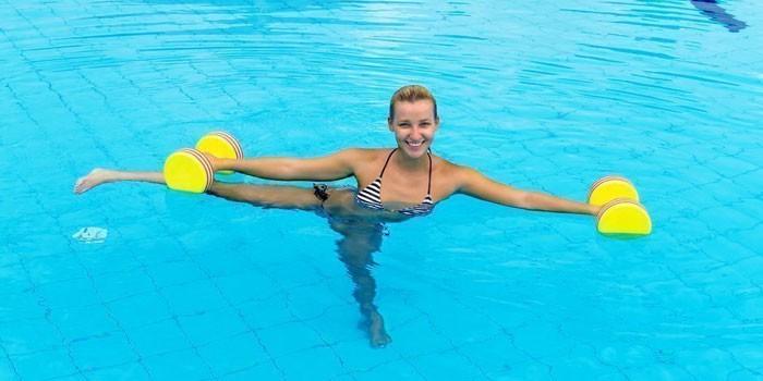 Девушка занимается гимнастикой в бассейне