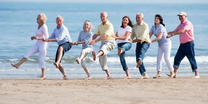Пожилые люди танцуют на побережье