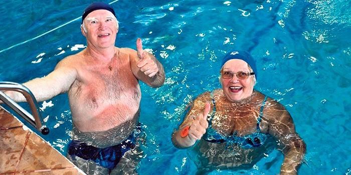 Пожилые люди плавают в бассейне