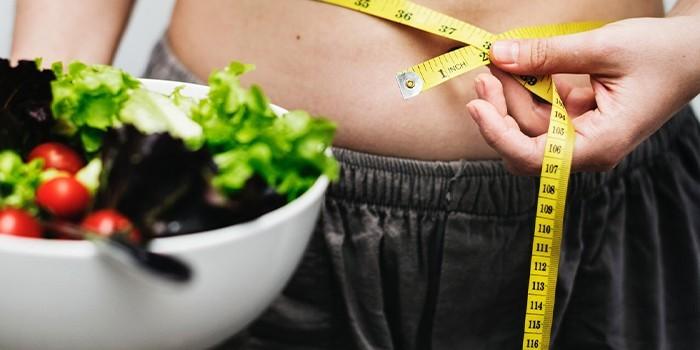 Женщина измеряет объем талии сантиметром